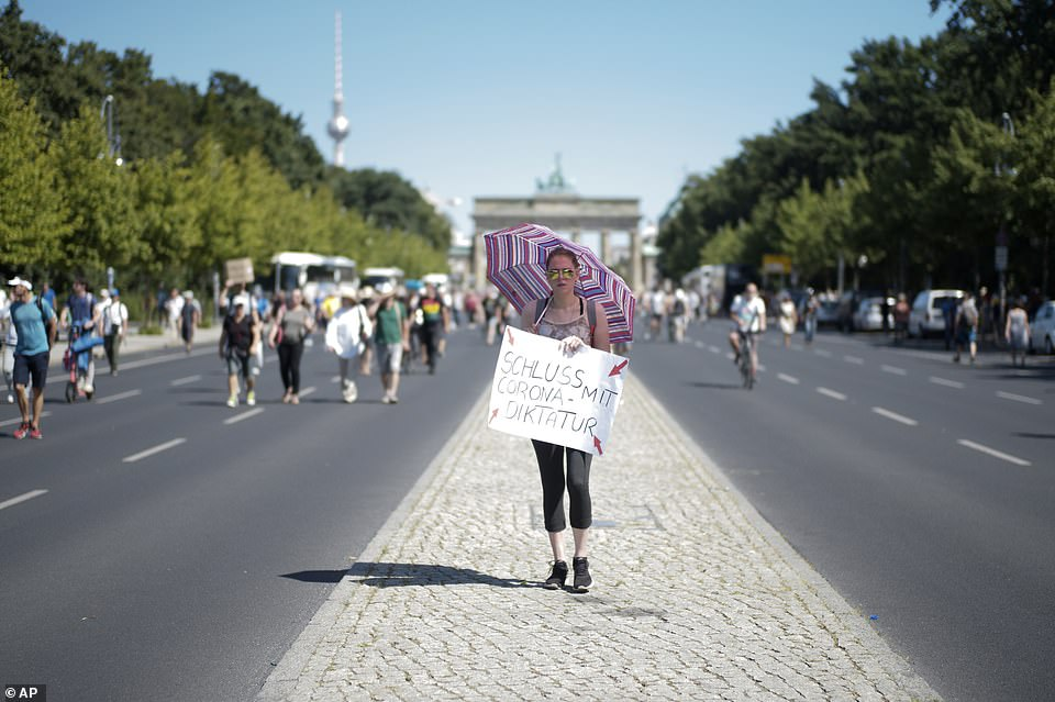 A woman carries a sign reading End of the Corona dictaturship